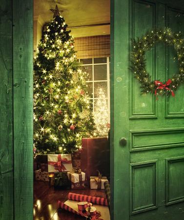 light: Apertura de la puerta rústica en una habitación con el árbol de Navidad Foto de archivo