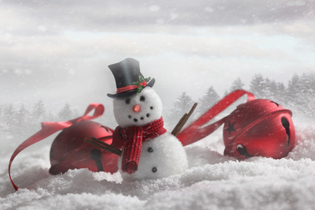 Snowman with bells in snowy winter background Stock Photo