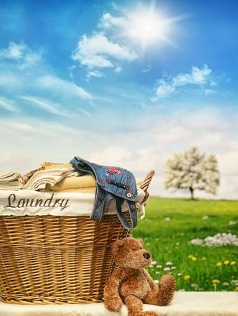 personal de limpieza: cesto de la ropa de mimbre con ropa contra un cielo azul