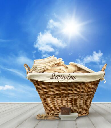 clean clothes: Laundry basket with clothes on rustic table against blue  summer sky