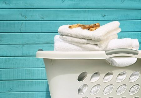 baskets: White laundry basket with towels and clothes pins