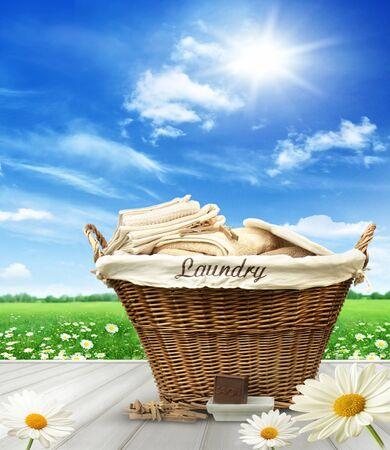 personal de limpieza: cesto de la ropa con la ropa en la mesa rústica contra el cielo azul del verano