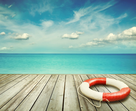 preserver: Wood pier with ocean and life preserver and blue sky in background Stock Photo