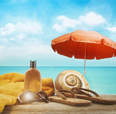 sunshine background: Suntan lotion with towel and sandals at the beach