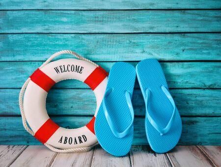 Blue flip flops sandals and life preserver on wood