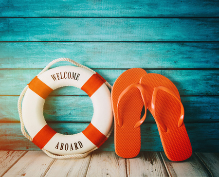 Red flip flops sandals and life preserver on wood Stock Photo