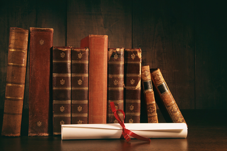 Stack of old books with diploma on wooden desk