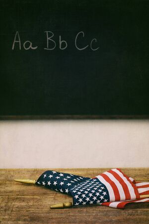 American flags laying on top of old school desk