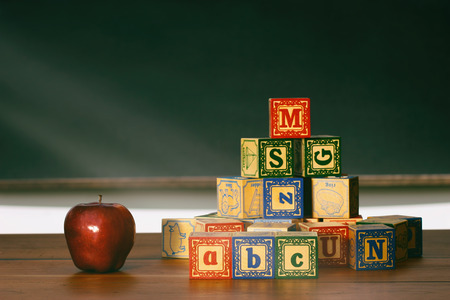 Wooden blocks and apple in front of chalkboard