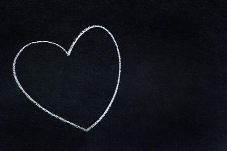 Heart shape written in white chalk on blackboard 免版税图像