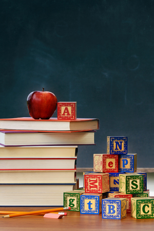 Stack of books with apple and wooden blocks in front of chalkboard
