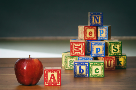 Closeup of wooden blocks and apple in front of chalkboard