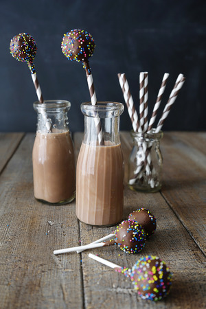 Bottles of chocolate milk with cake pops on table