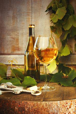 Bottle of white wine with glass on barrel 免版税图像