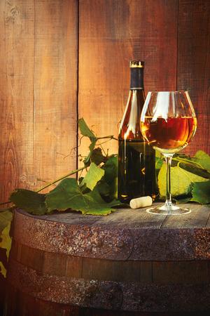White wine bottle and glass on old barrel 免版税图像