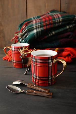 Plaid mugs with hot tea on wood table