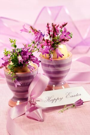 Purple flowers in egg cups for Easter 免版税图像