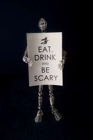 Wire mannequin holding festive halloween card 免版税图像