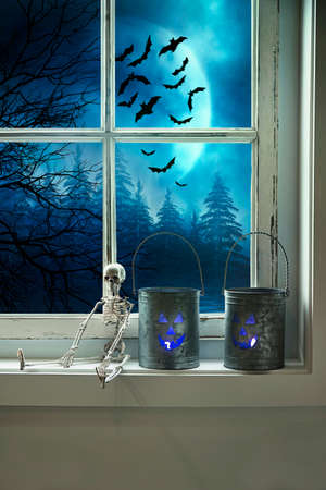 Metal tins with candles on window sill for Halloween 免版税图像