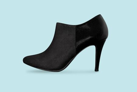 Black high heel shoe isolated on blue background