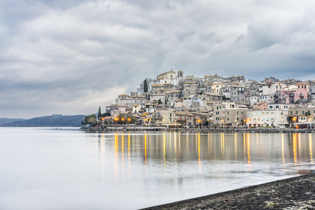 Italy, Bracciano, Anguillara Sabazia - 31 January 2016: It is a very cloudy morning but not very cold. This is the classic winter day on Bracciano Lake and Anguillara still sleeps in the background