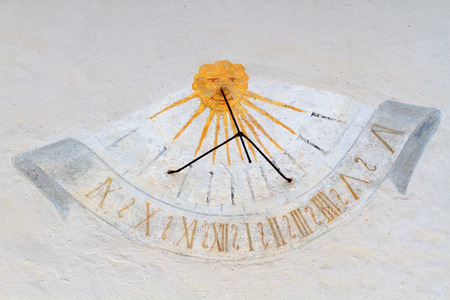 cheaper: Although nowadays is a rarity, a time tracked sundials on the external walls of buildings facing south were common, as they are visible from a distance and cheaper to build. Stock Photo
