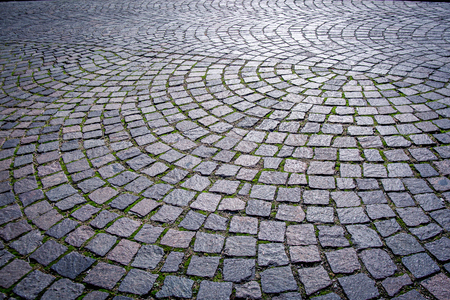 ices: Cobblestones anche Sanpietrini is the typical kind of pavement found in the center of Rome, Italy. It is made of bevelled stones of black basalt cobblestones, Placed one next to the other. It was invented under Pope Sixtus V and was used to pave all the Stock Photo