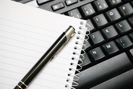 Pen and notebook over computer keyboard Imagens