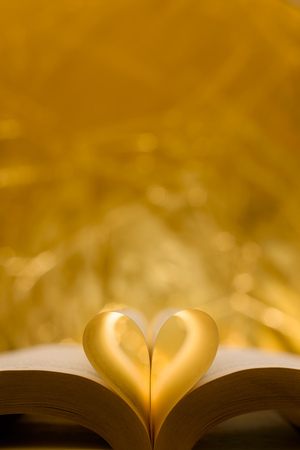 Heart-shaped paper inside a book. The shape of the heart is known worldwide as a symbol of love and unity. Imagens