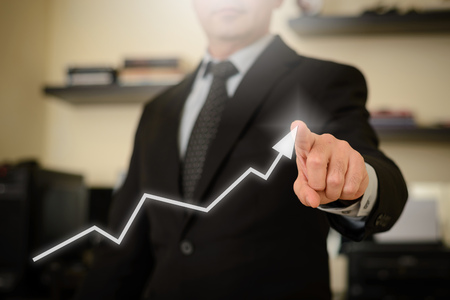 Business man showing success chart. This image represents positive thinking and plans for financial growth, success and victory.