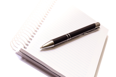 Pen on spiral notebook on white background