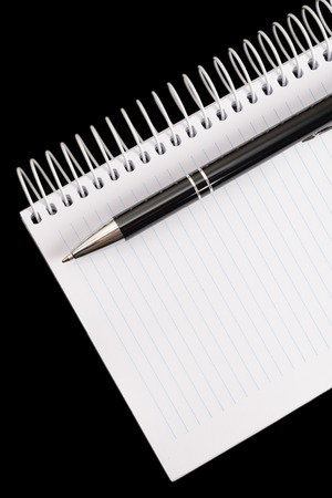 Pen and notepad on black background