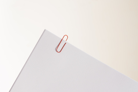 Some white papers clipped together. Represents reminders, documents or work papers.