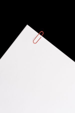 White sheet with clips on black background. Image represents reminder or group of documents. Banco de Imagens
