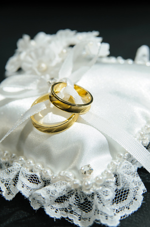 Pair of rings on white cushion. The rings represent the union of a couple. Imagens