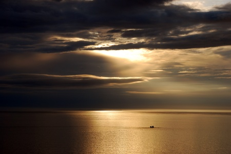 Lonely boat at sea by sunset