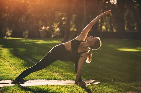 Beautiful young woman practices yoga asana Parivritta Parshvakonasana - Revolving side angle posture in the park Stock Photo