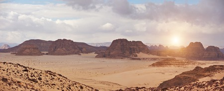 Valley in the desert with mountains at sunset