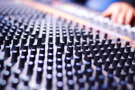 audio mixer: hand of dj on the soundmixer in the nightclub