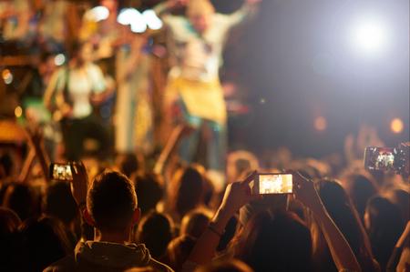 aplaudiendo: Audiencia con manos levantadas en un festival de música y luces que bajan desde arriba del escenario.