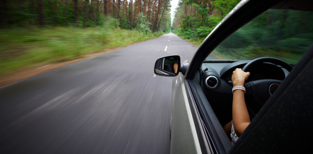 Young beautiful woman driving car - rear view