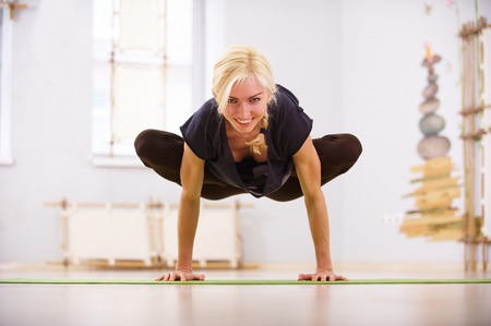 Beautiful sporty fit yogi woman practices yoga asana Padma Bakasana Lotus Crane pose in the fitness room