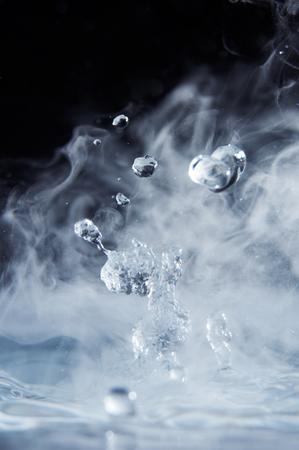黒の背景のクローズ アップに蒸気を沸騰水のしぶき