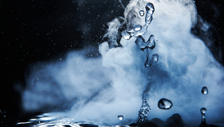 Kochendes Wasserspritzen mit Dampf auf schwarzer Hintergrundnahaufnahme