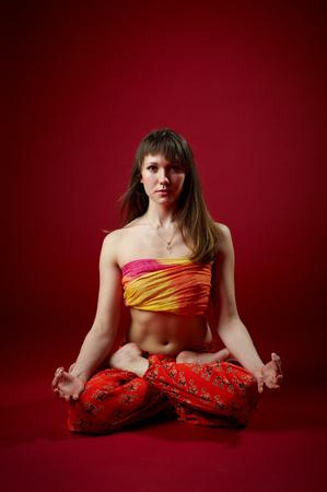 Beautiful sporty fit yogi woman practices yoga asana Padmasana - Lotus pose on the red background. studio shot