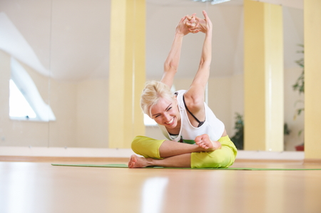 Beautiful sporty fit yogi woman practices yoga asana Adho Mukha Agni Stambhasana in the fitness room Stock Photo