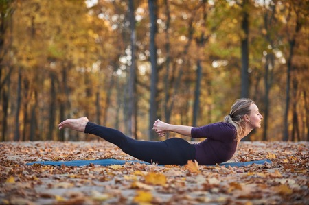 Beautiful young woman practices yoga asana Salabhasana locust pose on the wooden deck in the autumn park Stock Photo