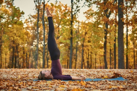 Beautiful young woman practices yoga asana Niralamba Sarvangasana - unsupported shoulderstand pose on the wooden deck in the autumn park.
