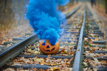 Smiling halloween pumpkin with bright blue smoke on the rails in the forest
