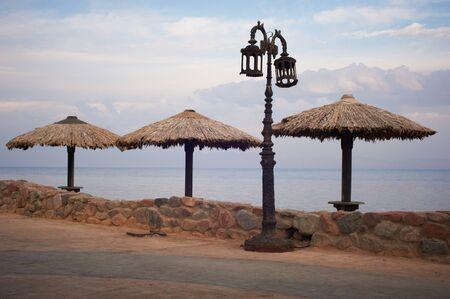 Empty embankment with straw umbrellas and streetlights in Dahab Stock Photo